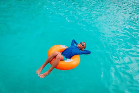 happy boy relax on floatie in pool Foto de archivo