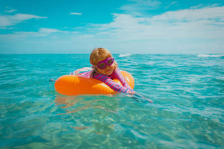 cute happy little girl swimming on floatie at tropical beach