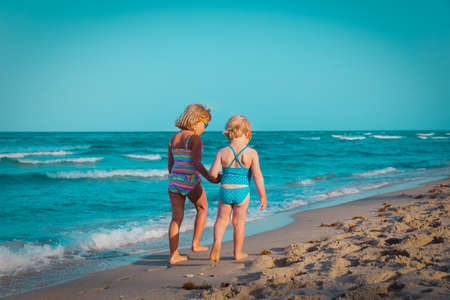 little girls walking on tropical beach, family at sea