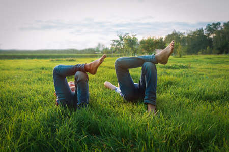 boy and girl relax on green grass, kids on summer vacation