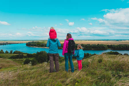 family looking at scenic nature, father, mother and kids travel in nature
