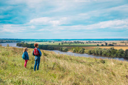 kids travel in nature, boy and girl enjoy scenic view Foto de archivo