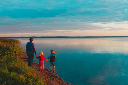father with kids on beach at sunset, family vacation in nature