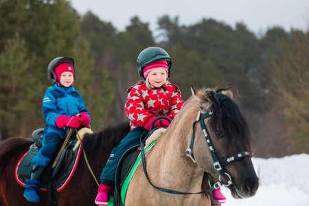 little girls on horse ride in winter nature Foto de archivo