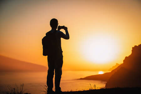 silhouette of a man holding a cellphone taking pictures outside during sunset in mountains