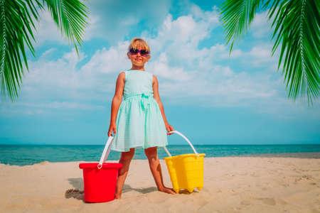 happy cute liitle girl play with sand on beach