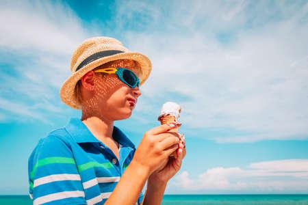 happy cute boy eating ice cream on beach