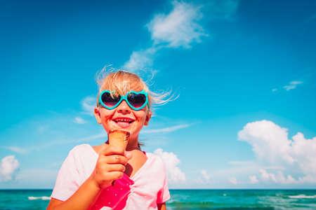 happy cute little girl eating ice cream on beach Foto de archivo