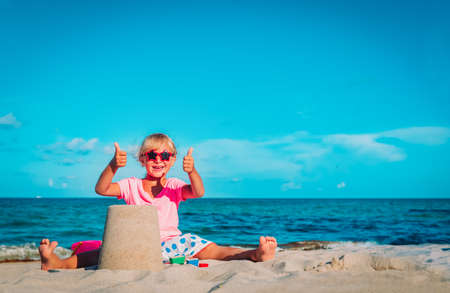 cute happy girl play with sand on beach Foto de archivo