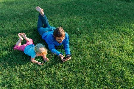 father and little daughter looking at mobile phone on green grass