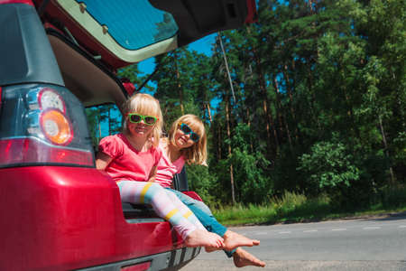 happy kids travel by car in nature, little girls on summer vacation Foto de archivo