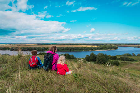 mother and kids travel in nature, family looking at scenic view