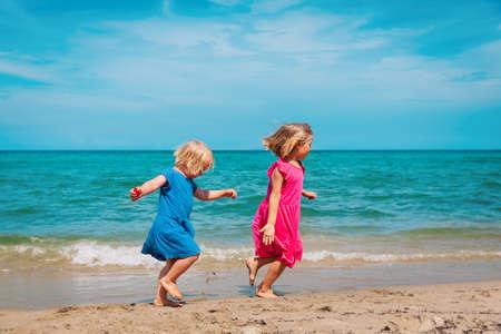happy cute little girls run and play at beach Foto de archivo