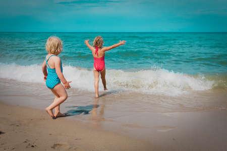 happy little girls swim on beach, family vacation