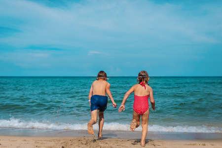 kids run to swim on tropical beach Foto de archivo