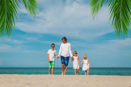 happy father and three kids walking on beach