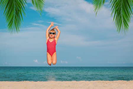 happy little girl play jump at beach Foto de archivo