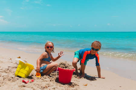 boy and girl play with sand on beach vacation