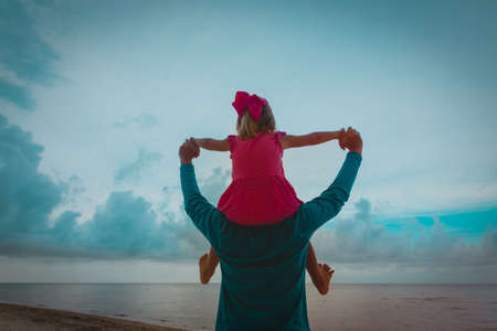 father and little daughter play on beach at sunset