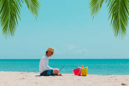 man with laptop on tropical beach vacation, family holiday at sea Foto de archivo