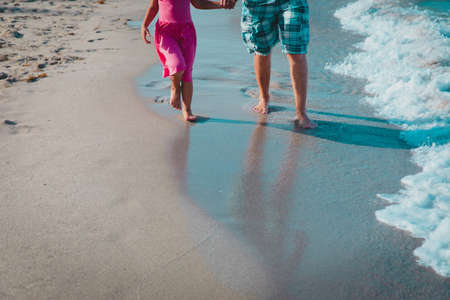 father and daughter walking on beach leaving footprint in sand