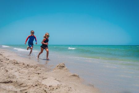 kids run, boy and girl have fun on tropical beach