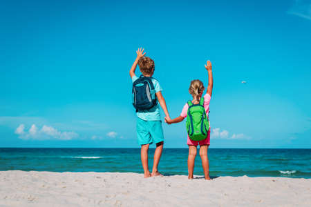 happy ravel on beach, boy and girls with backpack at sea