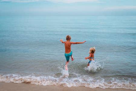 happy boy and girl run swim on beach Foto de archivo