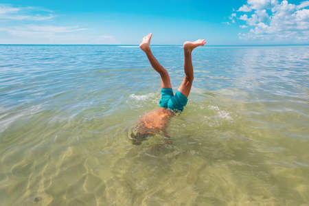 boy diving into water, kid making handstand in sea, vacation fun