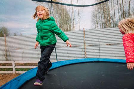 happy girls enjoy jumping on trampoline - outside in backyard
