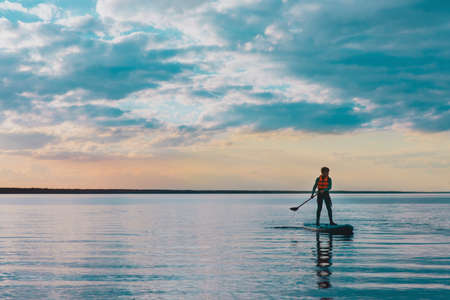 Kid riding on paddle sup surfboard in water at sunset