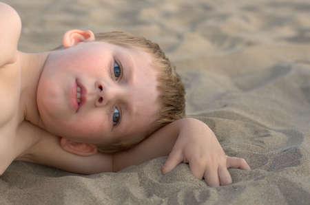 autism: thoughtful little boy on a sandy beach