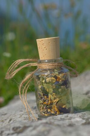 glass bottle with dried mountain herbs