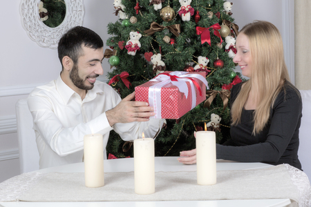 guy portrait: Portrait of a man and woman near the Christmas tree. Wife and husband sitting at the table.