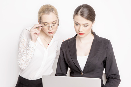 girl glasses: Two business woman on a white background. The business girl looks at the monitor and working. Stock Photo