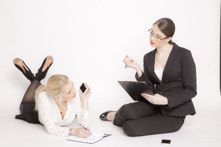 skirt suit: Two business women on a white background. Girl in costumes sit and work. Stock Photo