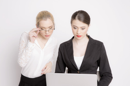 collectives: Two business woman on a white background. The business girl looks at the monitor and working. Stock Photo
