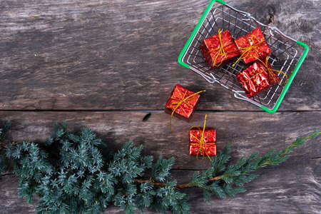 gift basket on a dark wooden background decorated with a juniper branch, coniferous branch.the concept of the shopping Christmas gifts. Stock Photo