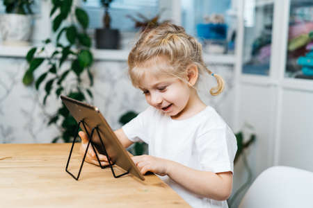 a little girl is sitting at a table with a tablet with her hands raised in the air smiling and happy, experiencing happiness Stock Photo