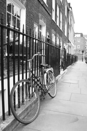 Bicycle leaning against railings in a London street
