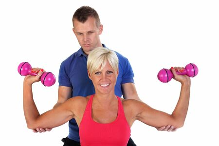 Attractive blonde woman doing shoulder-press with the support of her personal trainer photo