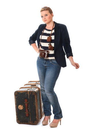 Pretty young woman heading on her travels with vintage camera and travel chest