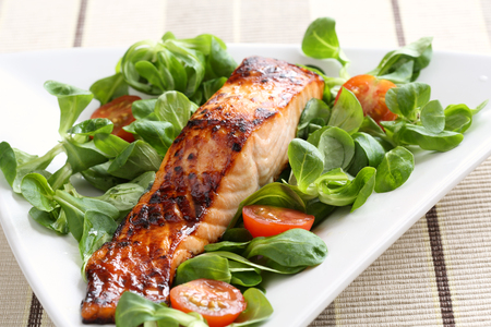 Grilled salmon with a honey glaze on a bed of lambs lettuce Standard-Bild