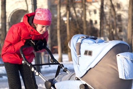 A young mother looks at the baby in a stroller for a walk in the park photo