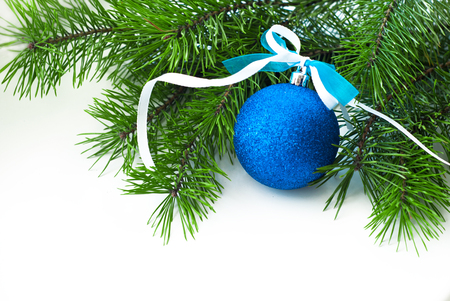 blue ball with decorative ribbon and Christmas-tree branch on white background photo