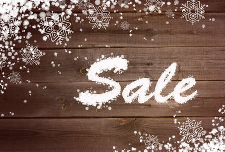 Winter sale background with snow and snowflakes on wooden surface photo