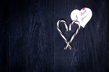 love confession: Love Confession and the heart of sweets on the dark wooden background