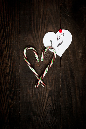 Love Confession and the heart of sweets on the dark wooden background photo