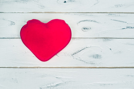 love confession: Red textile heart on white wooden background