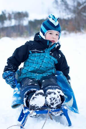 Happy boy in blue clothes sledding in snowing winter photo